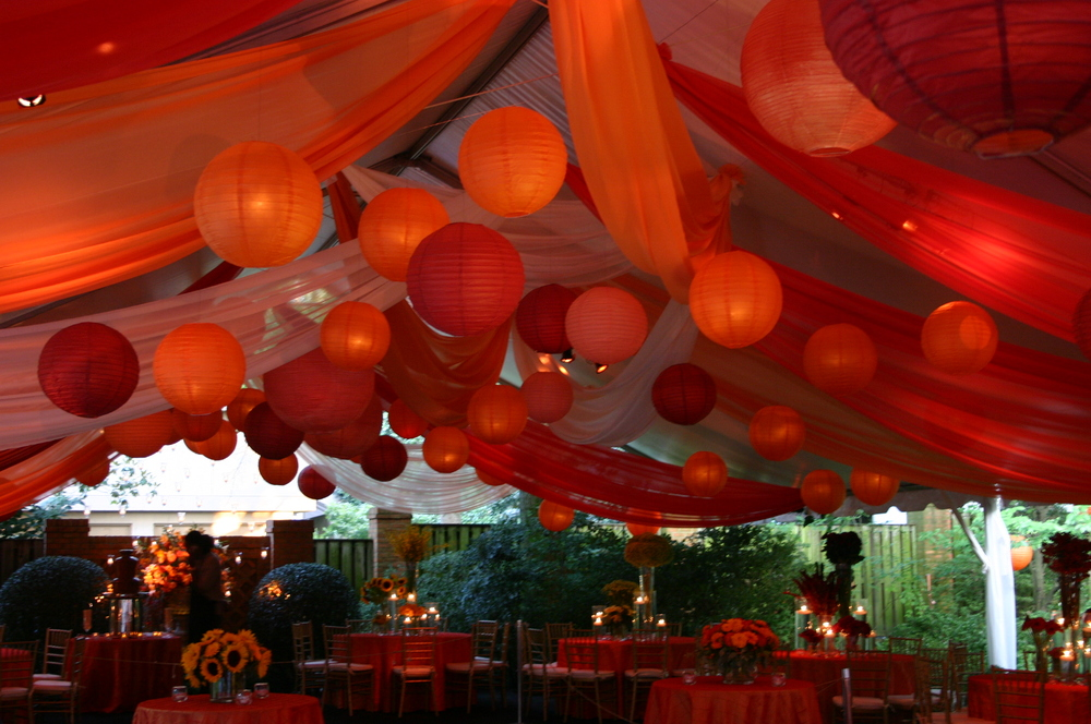 Colorful Chinese lanterns and fabric draping a tent by Amerispan Tents