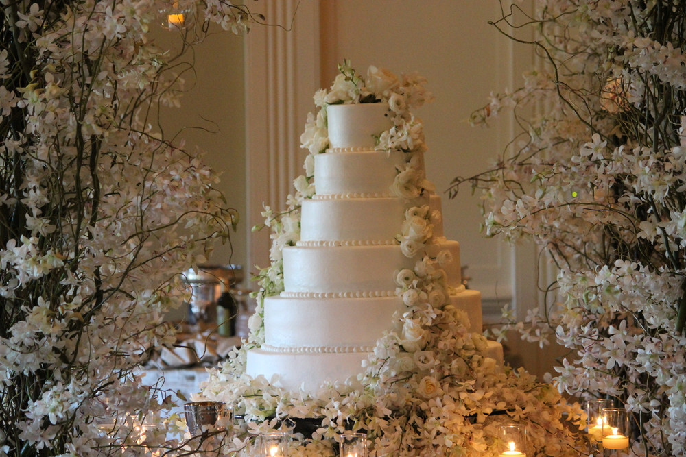 Wedding cake surrounded by an arbor of white Dendrobium Orchids at the Mephis Country Club. On the cake are Ranunculus, Roses and Orchids.