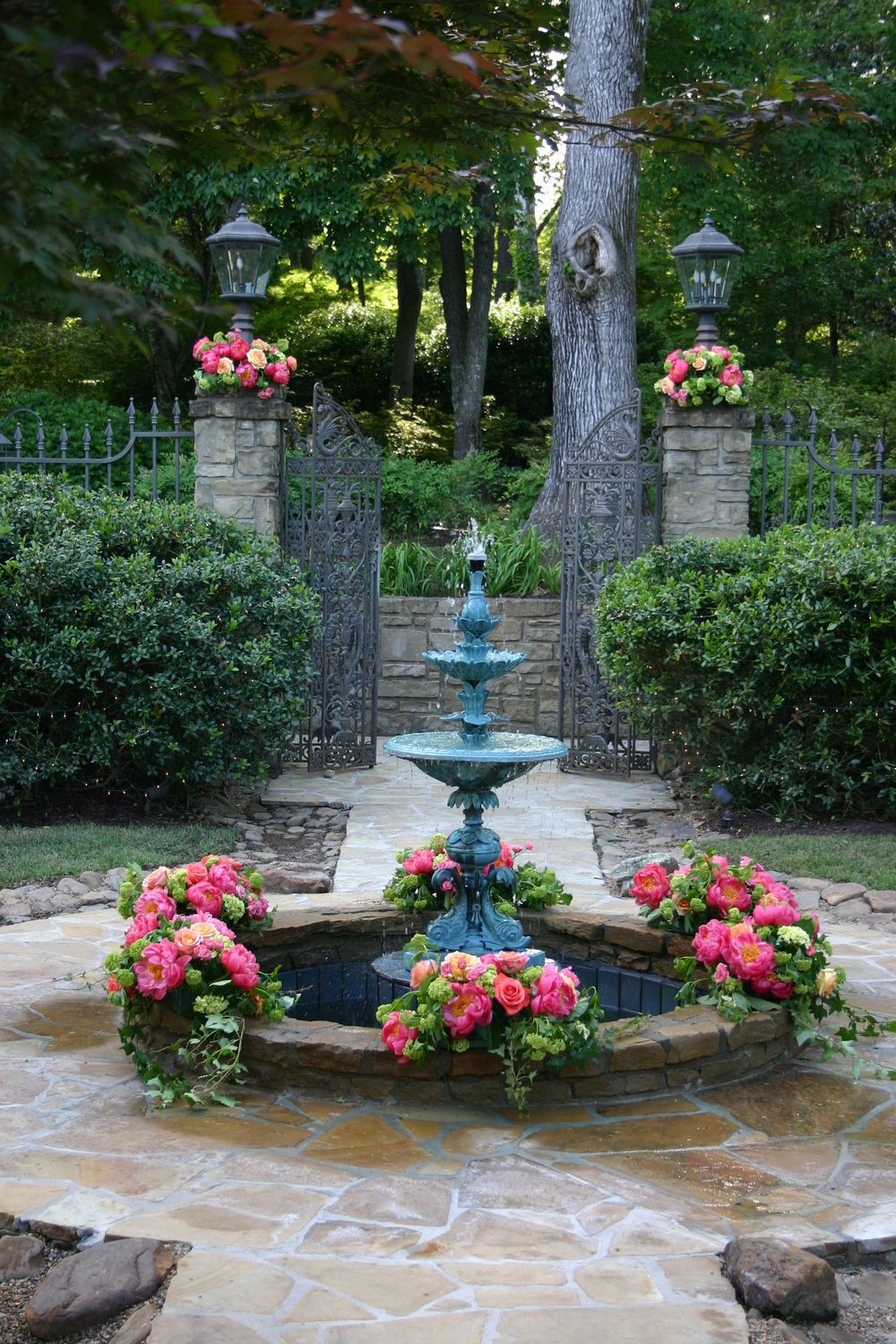 Fountain flowers including Coral Charm Peonies and Viburnum and a private home.