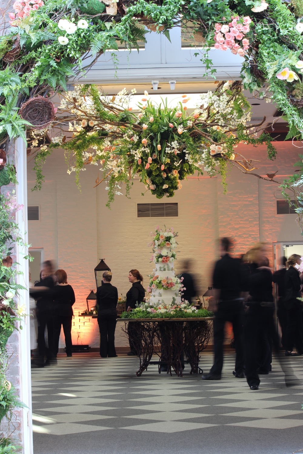Wedding cake under a hanging collection of Menton French Tulips, Ferns, Blooming Branches, Smilax Garlands and Roses in the Huges Pavilion at The Dixon Gallery and Gardens.