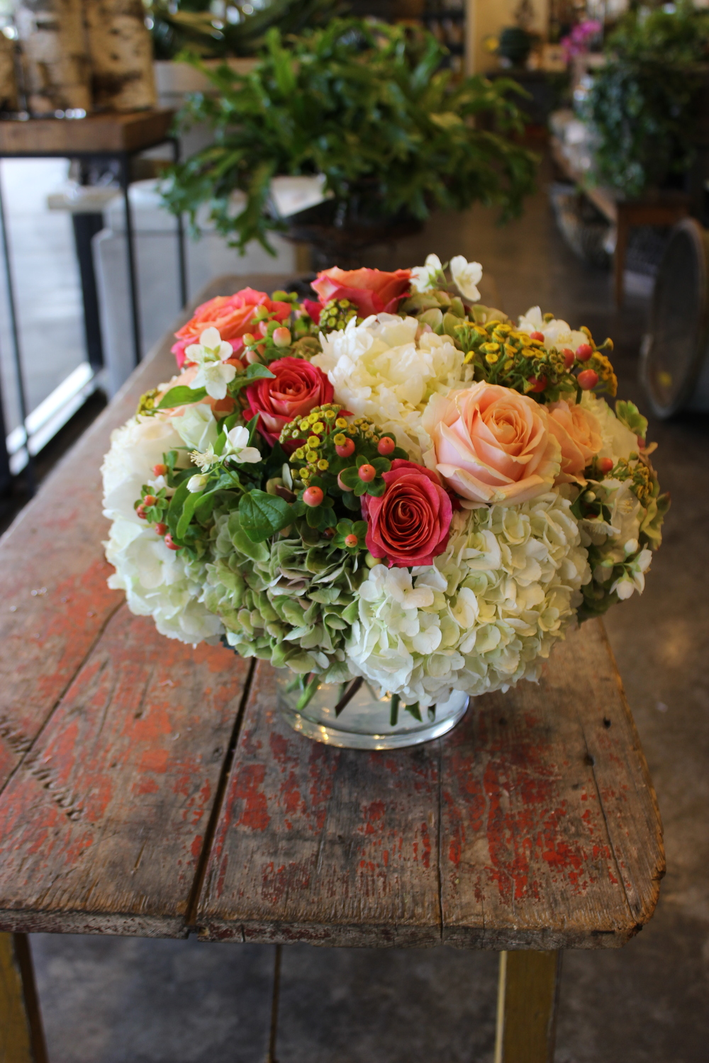 Low arrangement of seasonal fresh flowers starting at $100.00.