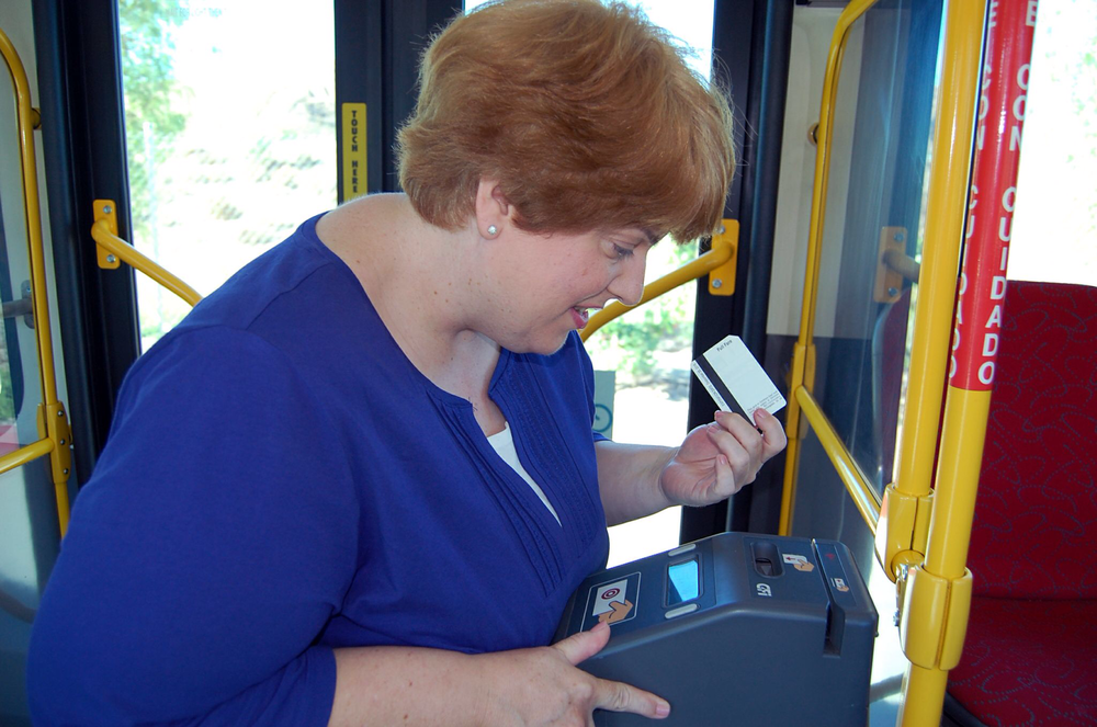 Picture of Connie looking at the fare box and paying for fare