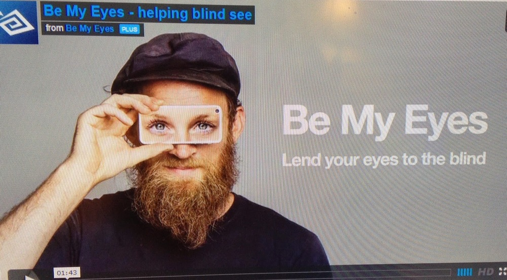 Picture of a man holding a piece of clear glass up to his eyes