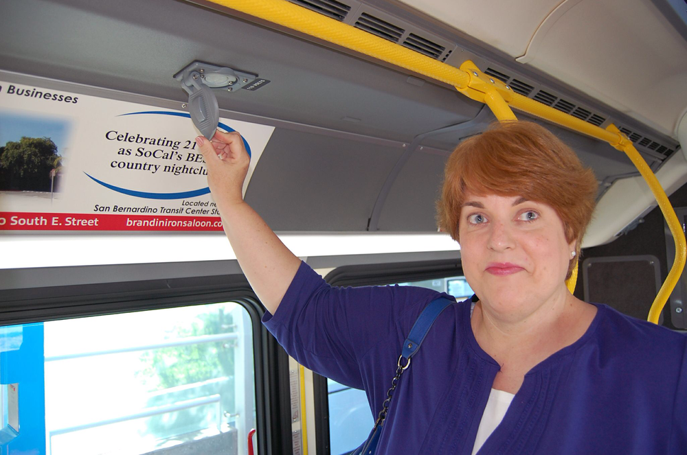 Connie pointing to bus ceiling outlet for charging laptops etc