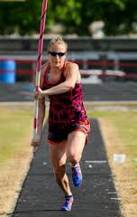 charlotte running on the track with a pole vault