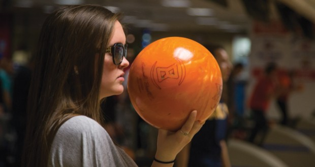 Fresno State student Shaela Warkentin, 19 holds her bowling ball as she gets assistance from Coach Duncan in her bowling class.