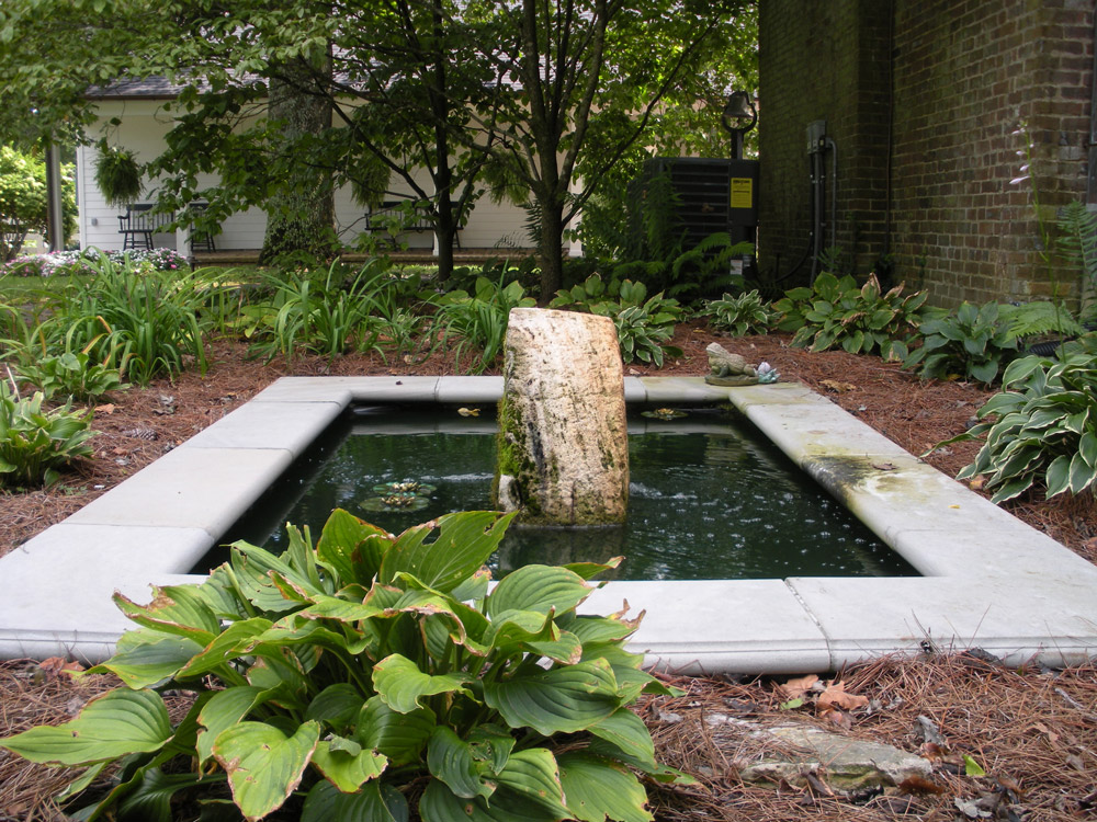 Koi pond with limestone coping and a vertical antique Millstone