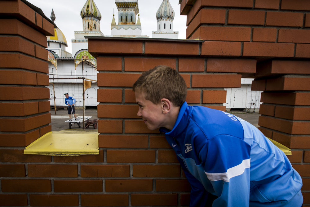 A boy takes cover behind a brick fortress as another searches to find him during a game of Hide and Seek at the Izmailovsky flea market in Russia on June 5, 2015. (© Alicia Afshar)