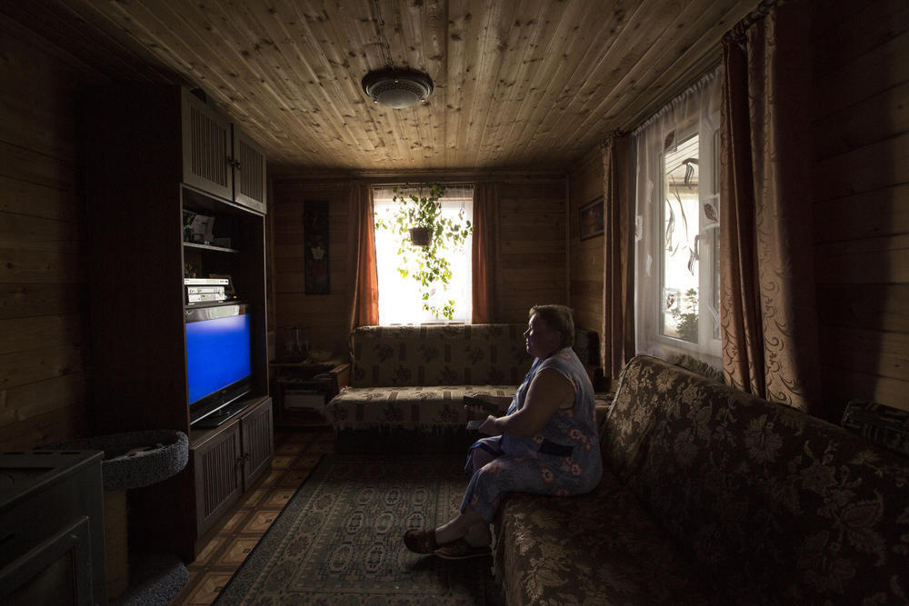 Nadezhda Usopovna Kiresheva works day in and day out on the farm, feeding the animals, cleaning up after them, weeding the garden, planting vegetables, and many more tasks. Nadezhda takes a break from working to watch a soap opera on Tuesday morning, June 2, 2015, in Goritsa, Moskovskaya, Russia. (© Alicia Afshar)