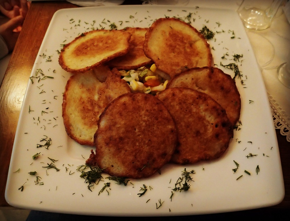 "1st potato pancakes in Poland, but...  ...not my last. I am an ovolactovegetarian which means I don't eat meat or fish, but do eat eggs and dairy.  The concept of vegetarianism is understood and easily communicated with phrases like: "" Jestem wegetarianką""  (I am a vegetarian) and "" Czy w tym jest mięso? "" (Is it with meat?)  Unfortunately, vegetarian dishes were difficult to find so my go-to dish became potato pancakes and other potato dishes. Delicious at first especially the dish you see here, but no more potatoes for me for quite some time."
