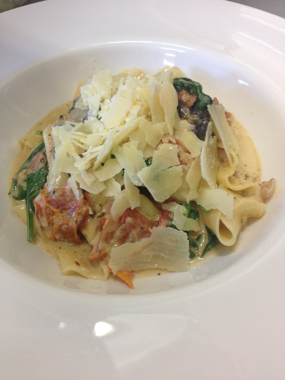 Freshly made Pappardelle with bacon, mushrooms, spinach and semi-dried tomatoes with in creamy white wine sauce with pecorino cheese