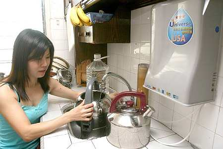 June collecting water through a water filtering system in her apartment in Jalan Mesjid Ngeri.