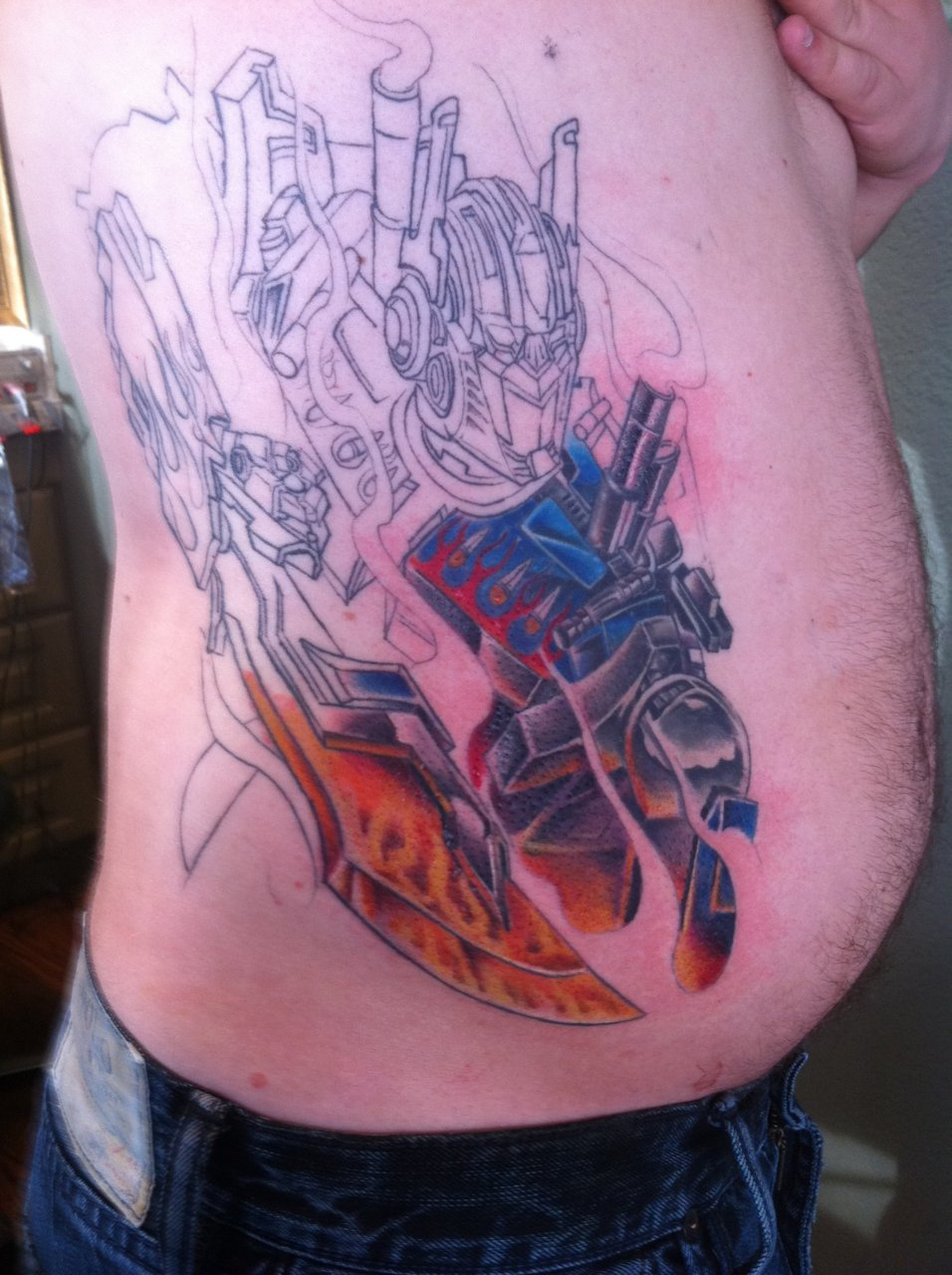 Presented without comment. #nightmarefuel #manchildren #okaymaybetwo    fuckyeahtattoos :     Partially finished Optimus Prime. This was a tattoo I debated over for close to two years. I'm a huge Transformers fan and have been since I was about 8. Can't wait to get it finished! I got it done by Dennis Hamilton at Frontline By The Sea in Cardiff, CA. He is the man! Such thorough detail. This tattoo is about 8 hours in.