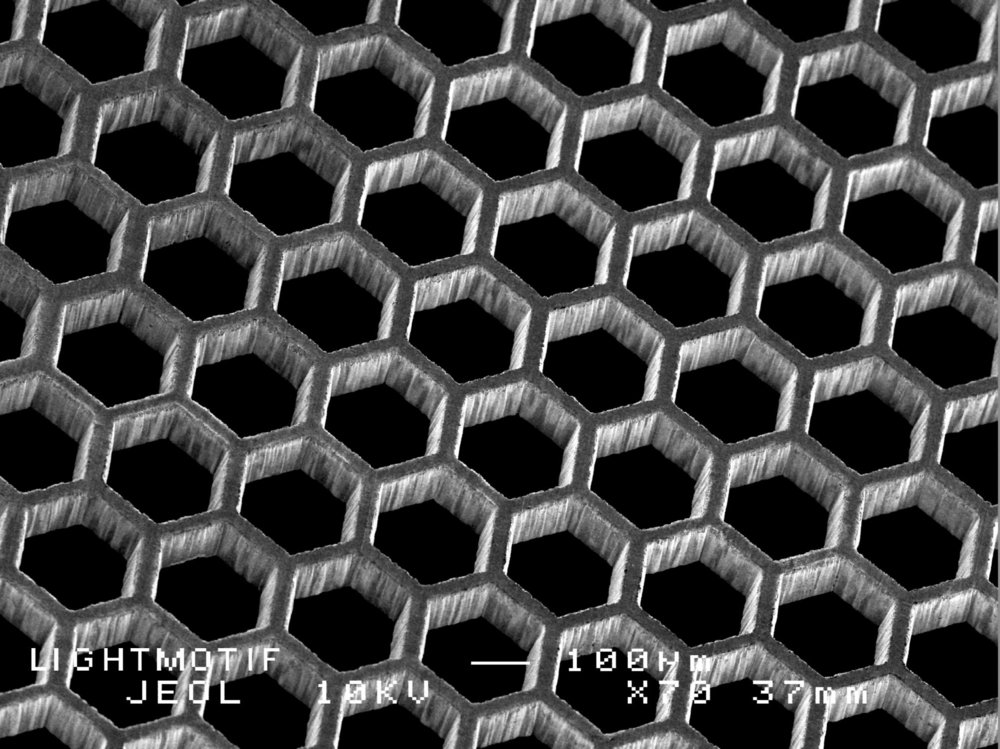 SEM image of hexagonal patterns laser cut in stainless steel sheets.