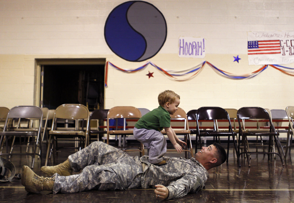 Adam Evans of Roanoke, Va. plays with his step-son, two-year-old Allen Webster, when Evans returns home after serving in Iraq. 105 National Guard members were dismissed at the National Guard Armory in Christiansburg, Va.