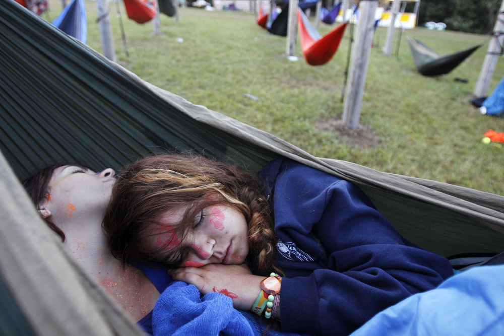 Sarah Williams (left), 19, and Bella Reyes, 18, both of Charlottesville, Va., rest in an Eno hammock during the early morning hours of FloydFest in Floyd, Va.