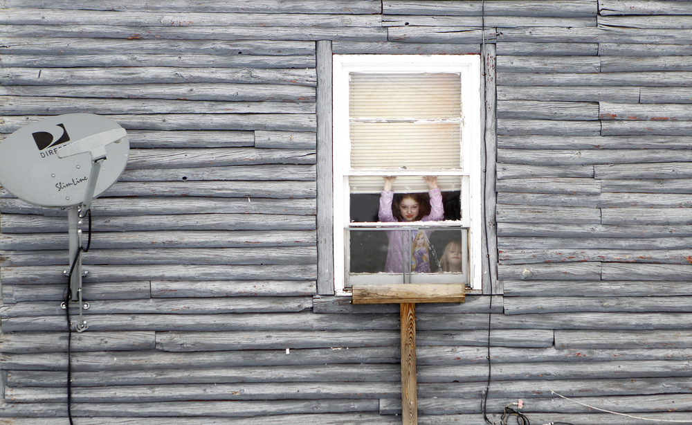 Savanna Cotts (left) and her sister, Sky, peek out of a window from inside their Goshen home.