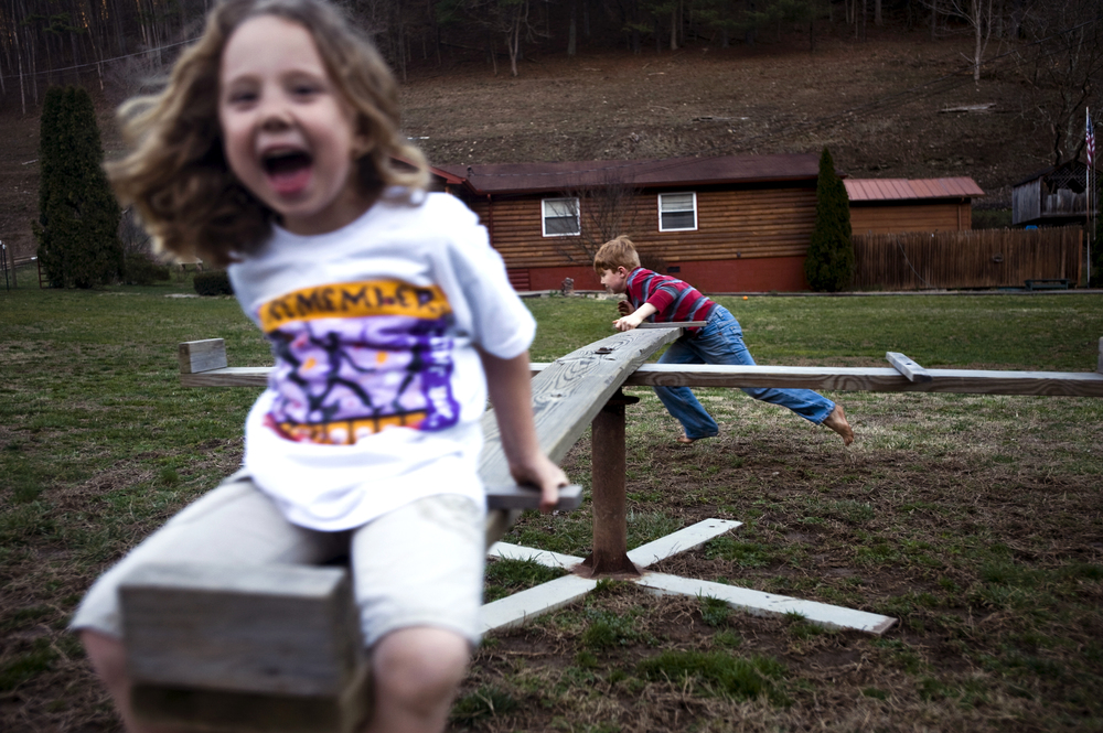 Six-year-old Pammy Collins, and her brother, nine-year-old Christian, play on the merry-go-round at their grandparents' house. Pammy and Christian lived with their grandparents, Pam and Jimmy McIntosh, in Whitesburg, Ky.