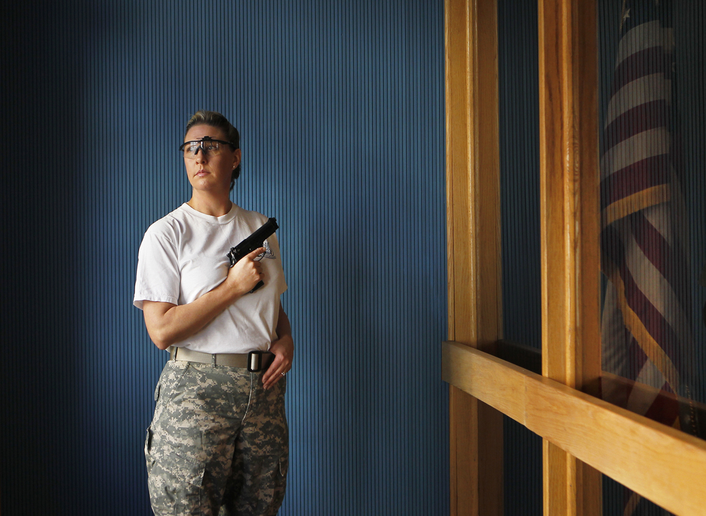 """Kimberly Eakin, 45, of Roanoke County, is photographed with a Beretta 9mm. """"I've been shooting since I was 12,"""" Eakin said. """"I actually joined the military because I wanted to shoot for a living. """"Pistol shooting is a mental sport. It doesn't matter if you're male or female, black or white or purple, skinny, tall, fat, short; it just doesn't matter. It's just concentration and making yourself into almost a machine that delivers the shot down range in the center of the target time after time after time."""" Eakin broke eight national records, four of which still stand.   See full project here."""