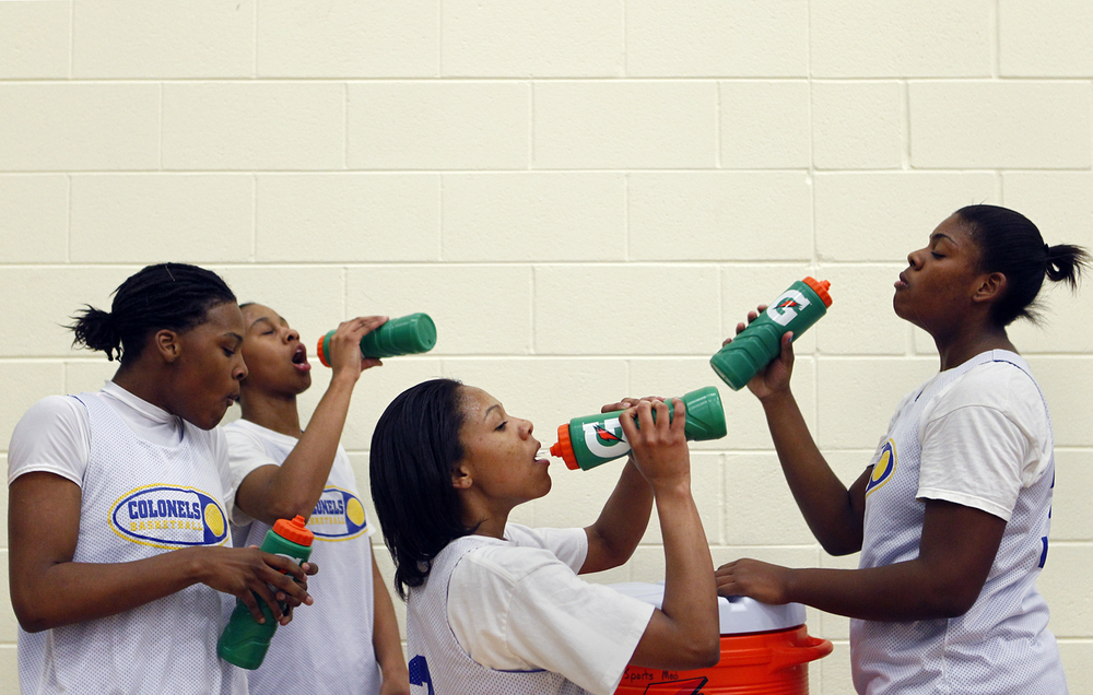 William Fleming High School basketball players get a drink during a team practice in Roanoke, Va.
