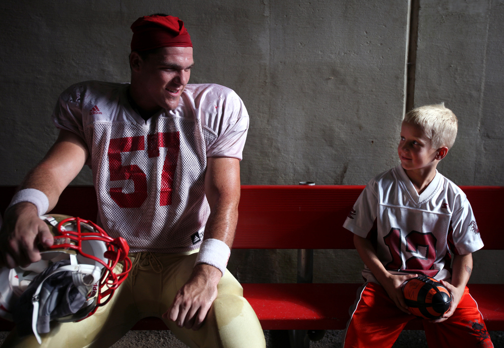 VMI redshirt sophomore linebacker Weston Reber of Huntersville, N.C. chats with the team's water boy, Jacob Campbell, 7, of Lexington, Va., while the team seeks shelter at Alumni Memorial Field during a lightning delay.