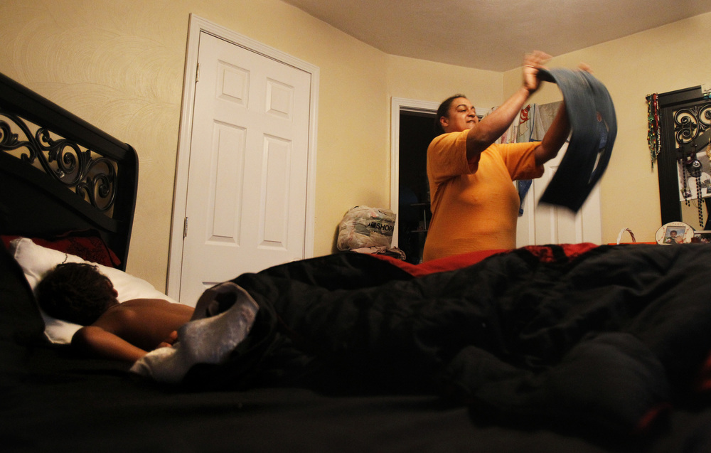 "Shannon quickly folds a pile of laundry while waiting for her youngest son, Andre, to get out of bed and ready to go to daycare. Shannon said she lived the ""street life"" for 25 years, and started working her way up from a job at McDonald's. ""You don't have to die in the streets,"" she said."