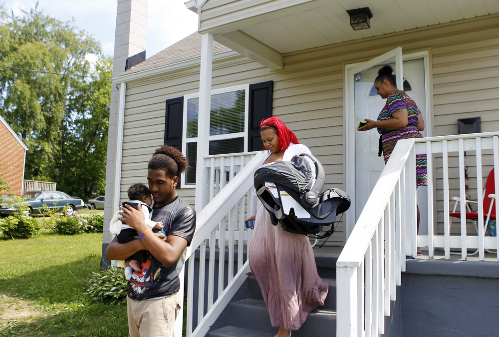 "Cursean Austin (from left) walks his nephew Kay'Mari Barber to the car while his sister (Kay'Mari's mom) Sharontay Huff, 20, and their mom, Shannon, leave Shannon's Roanoke home on their way to Refuge Temple Church-Our Lord for Sunday church. Shannon said she lived 25 years of her life living the ""street life,"" and faith helped her grow into the person she is now. ""If I ain't known nothing about God, I wouldn't be here now,"" she said. ""At the end of the day, I know I have my own personal relationship with God."""