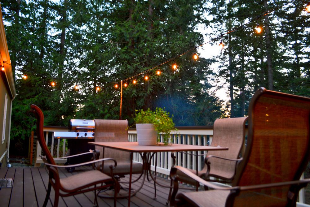 Rear deck with patio, grill and lighting create a tranquil ambiance.
