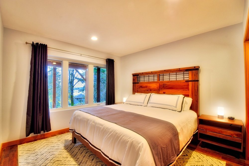 Guest bedroom # 1 features a king-sized bed with great views.