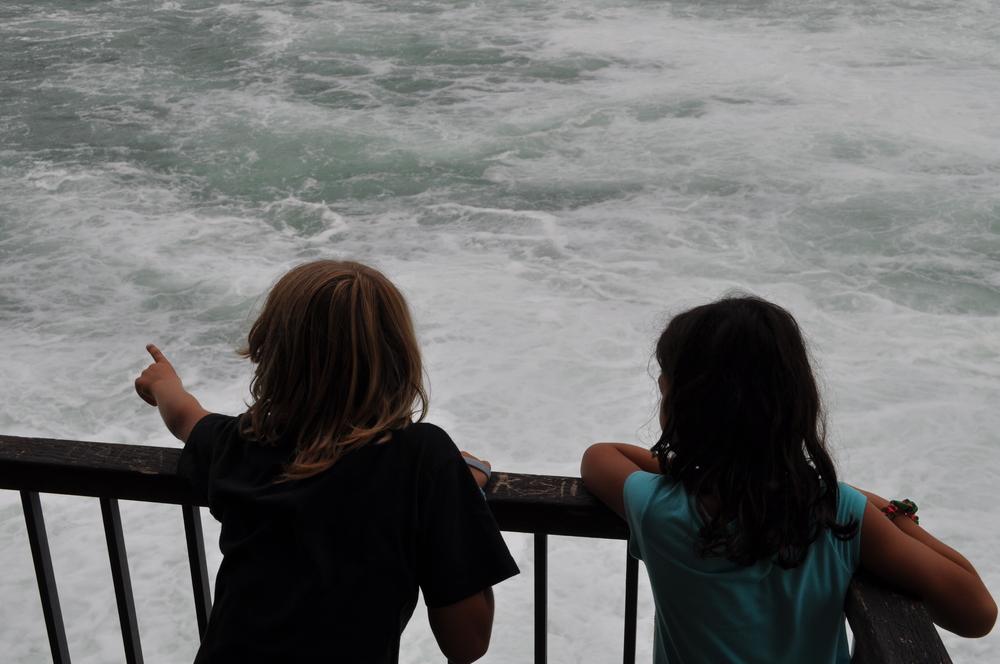 Los niños tiran una pequeña rama caída para visualizar la fuerza de la corriente. Foto: Bruny Nieves