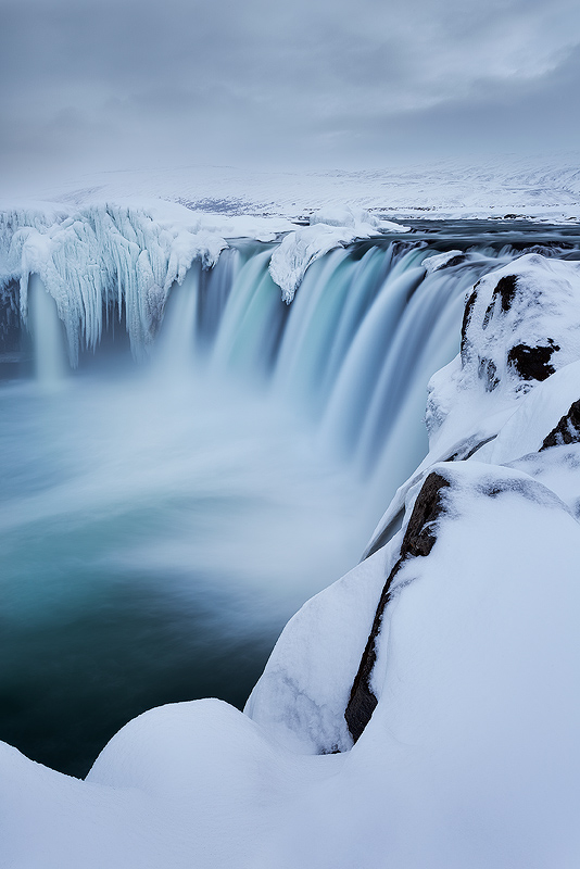Godafoss Waterfall in Iceland. Freezing spray made this spot impossible to photograph a few days before this image was taken. I admit to using a credit card to scrape the ice of my filter, a practice I do not recommend.