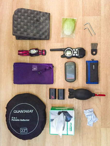 Landscape photography accessories, starting from top left: foam knee pad, hotel shower cap, tripod wrenches, headlamp, walkie-talkie, brush for cleaning up small scenes, microfiber towel, hiking GPS, memory card holder, Canon batteries, rocket blower, portable reflector, Kim Wipes, and silica packs.