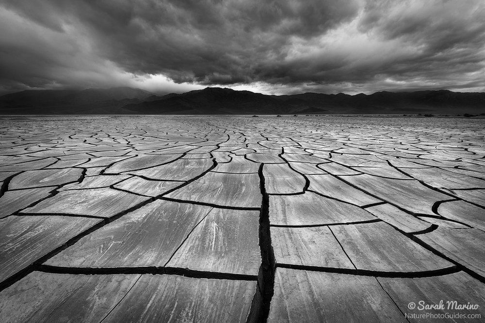 An incoming storm over large mud tiles in Death Valley National Park.