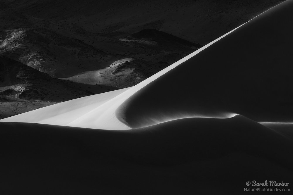 The last light of the day illuminates a ridge on remote sand dunes in Death Valley National Park.
