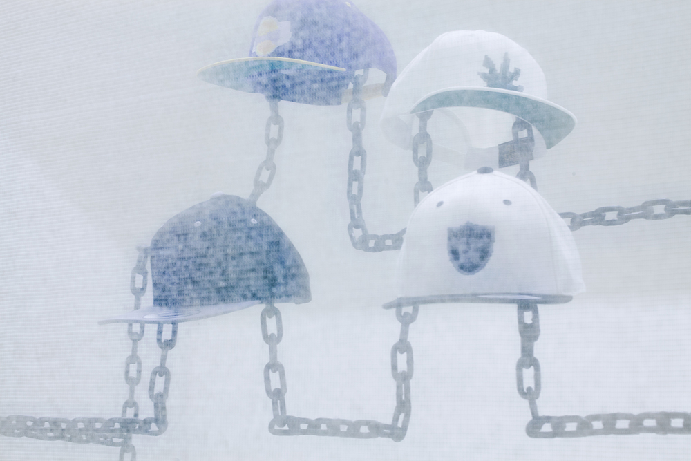Robin Jiro Margerin  Express yourself (Chain gang)  2014 Six digitally blurred logos embroidered on classic snap-back caps, welded steel chain, color inkjet print Courtesy of the artist