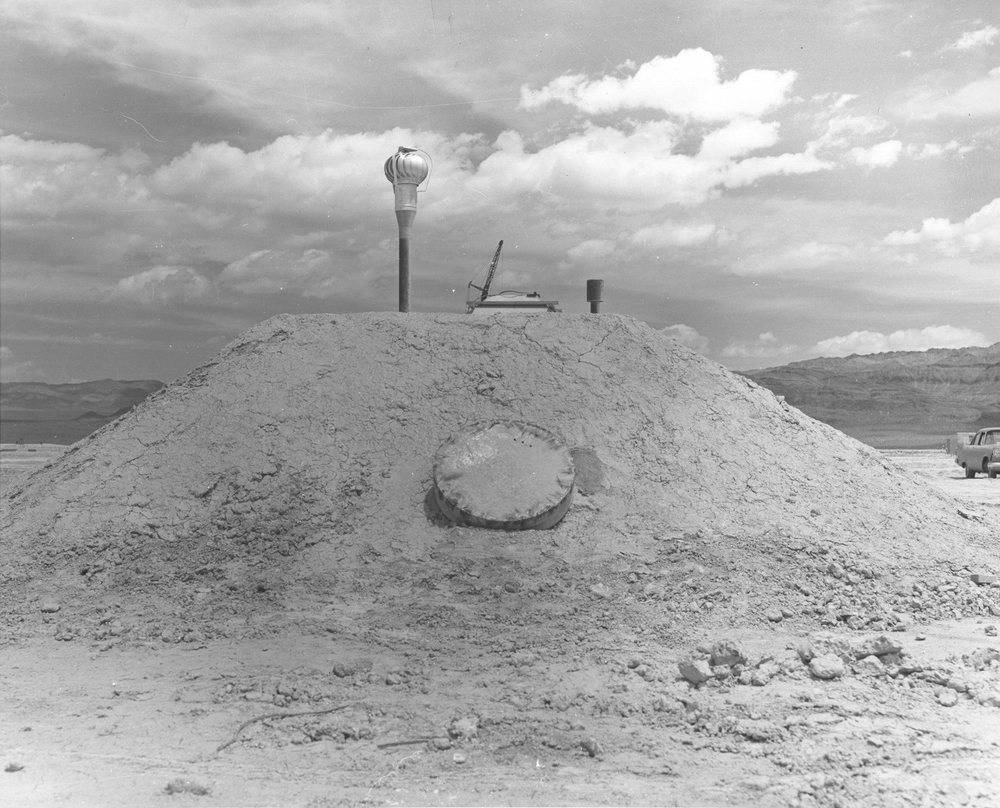 1957 - NEVADA TEST SITE -- Rear view of a family-type shelter designed by the Federal Defense Administration. 3 steel reinforced concrete shelters with earth covering will be tested at pressure ranges of from 30 to 65 pounds per square inch. The escape hatch is shown, with cover in place. Above it is the air exhaust pipe, to the right is the tip of the air-intake pipe. National Nuclear Security Administration / Nevada Site Office