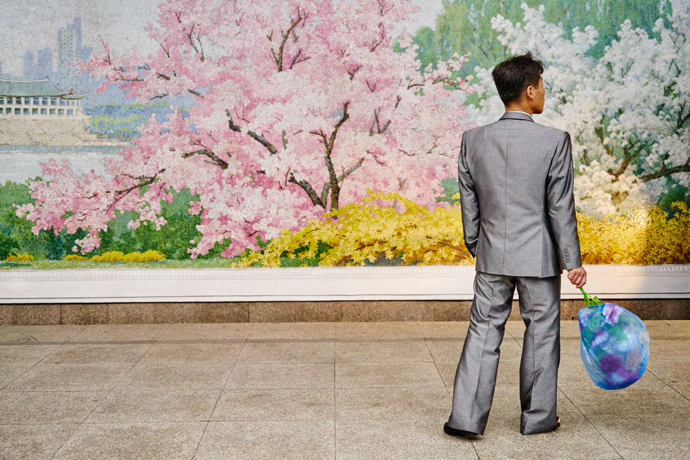 A well-dressed man waits with a bouquet of flowers at the Pyongyang Metro.
