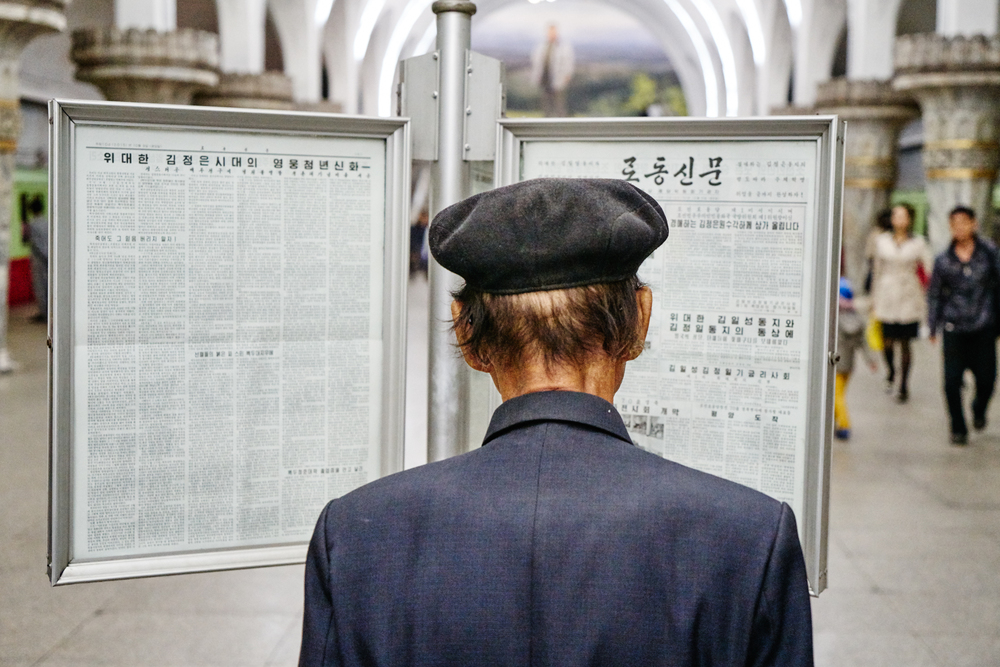 Reading the daily news, Pyongyang metro station.