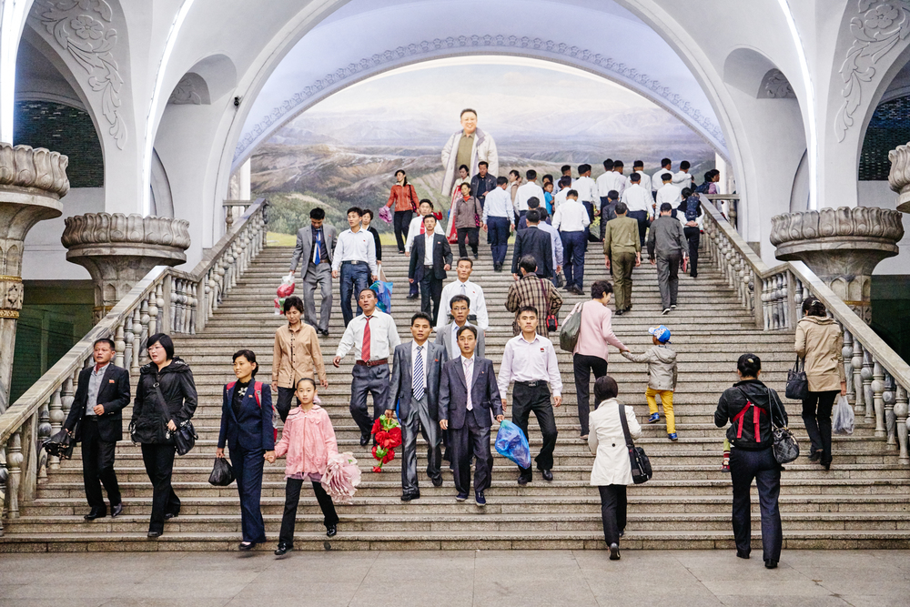 A huge mosaic wall of Kim Jong-Il looms over the staircase inside Pyongyang Metro Station.