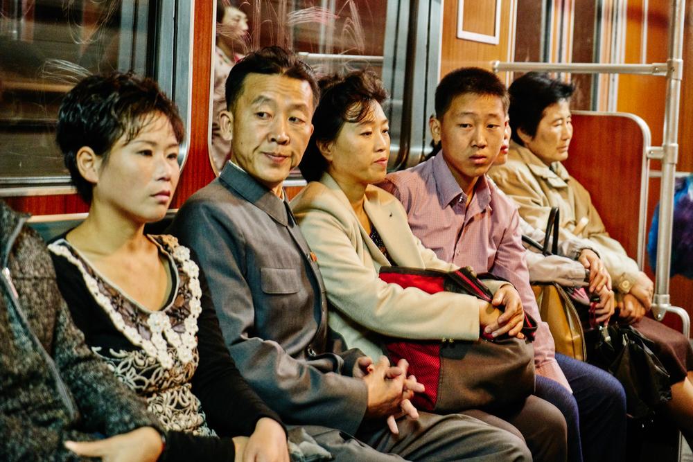 Daily commuters inside the Pyongyang metro car.