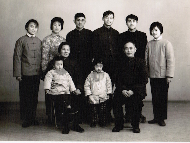 I was four years old, and my brother was three. The back row from left to right: my auntie, my parents, my younger uncle, my older uncle and his newlywed wife. My grandparents sat in the front row. My brother wanted to run away, so my grandma put him on her lap and held his hand. I was the good girl, furtively playing with my coat and exploring my pocket.