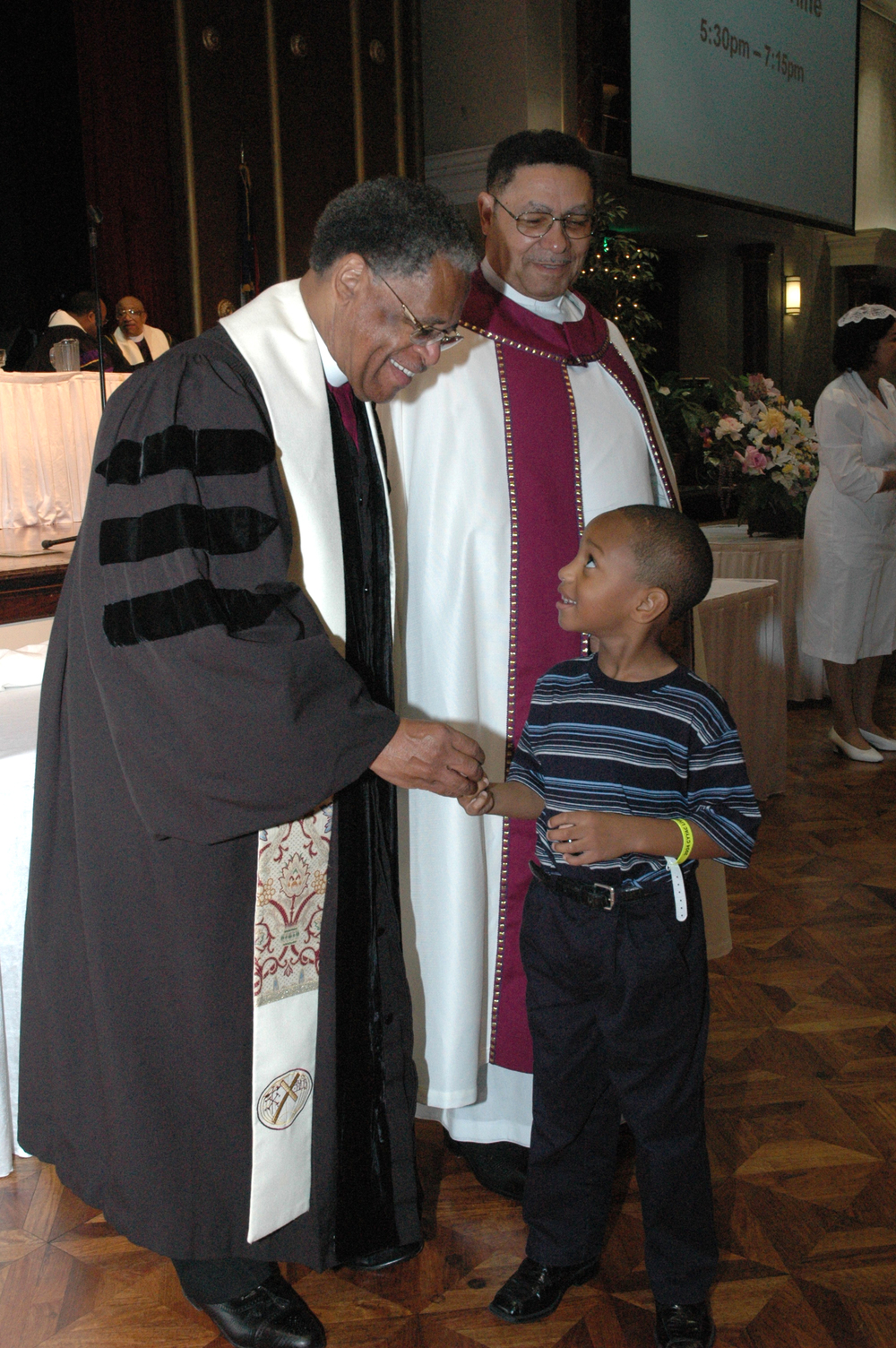 Two CME Bishops give Communion to a child at the CME youth a.JPG