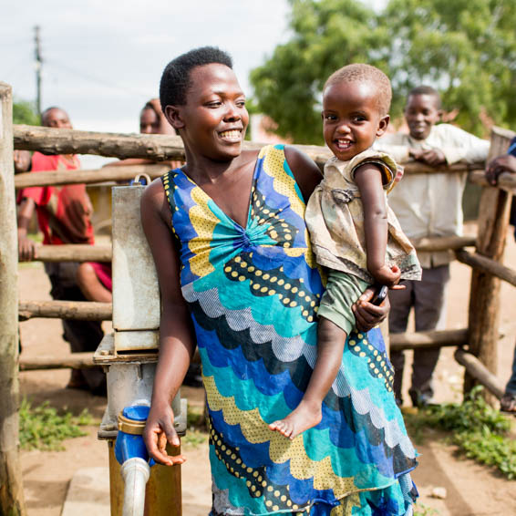 Rabecca with her daughter. She was hired as one of the first water caretakers in Uganda.