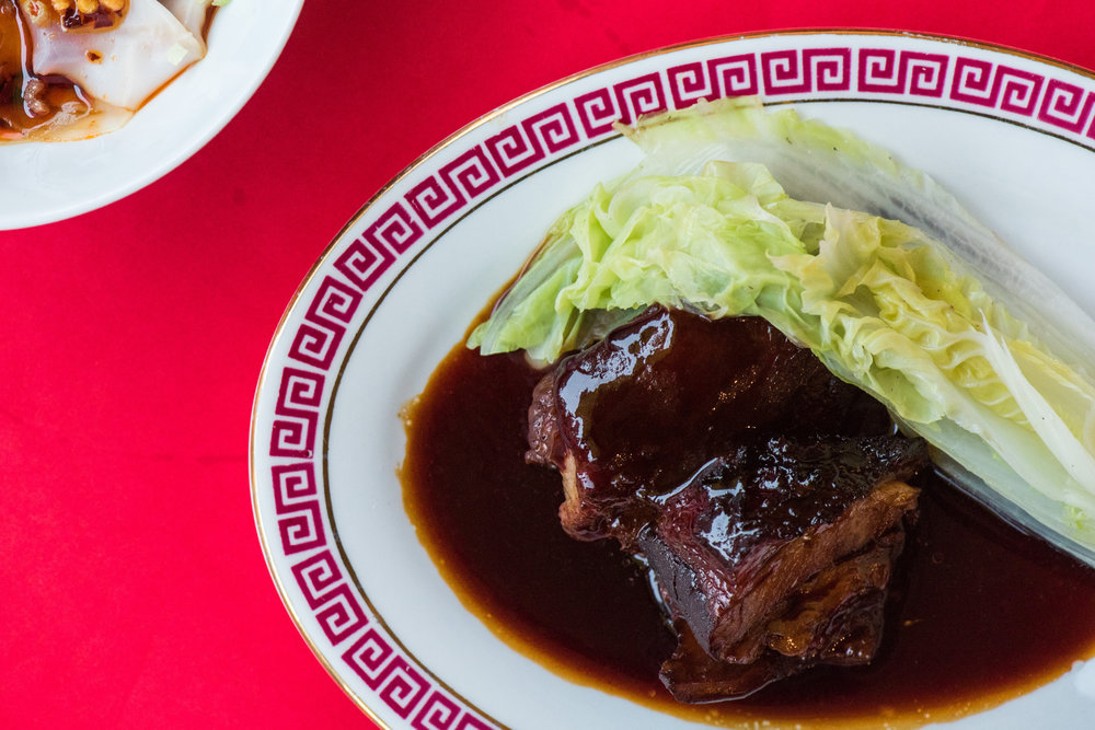 There's no soy sauce,  the red color comes from a caramel. in the absence  of soy sauce, the other spices  have a bit more room to shine., producing a pork belly that's wonderfully succulent and nuanced.