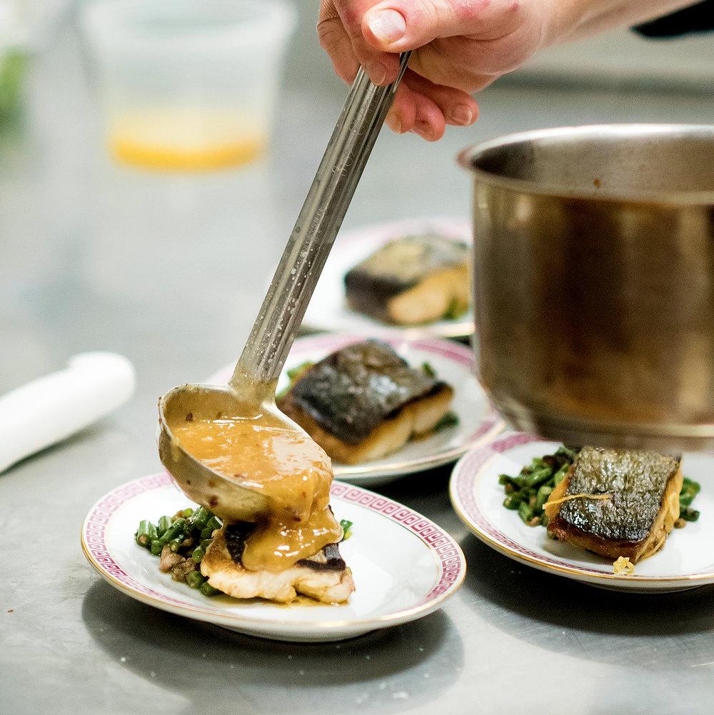 plating the 3rd course: west lake cod, leeks, snail black vinegar, potato