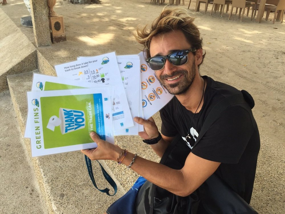 A Green Fins partner holding some laminated posters that they use for guest briefing.  (Photo via the Green Fins website)