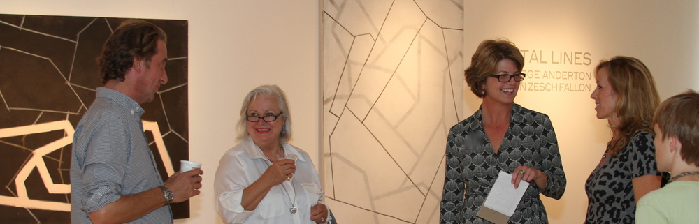 Featured Artist George Anderton (L) talks with exhibition visitor, Ms. Fallon, while curator Kathy Gibson greets art dealer Susan Baisden and her son Evan, standing in front of works by Gwyn Zesch.