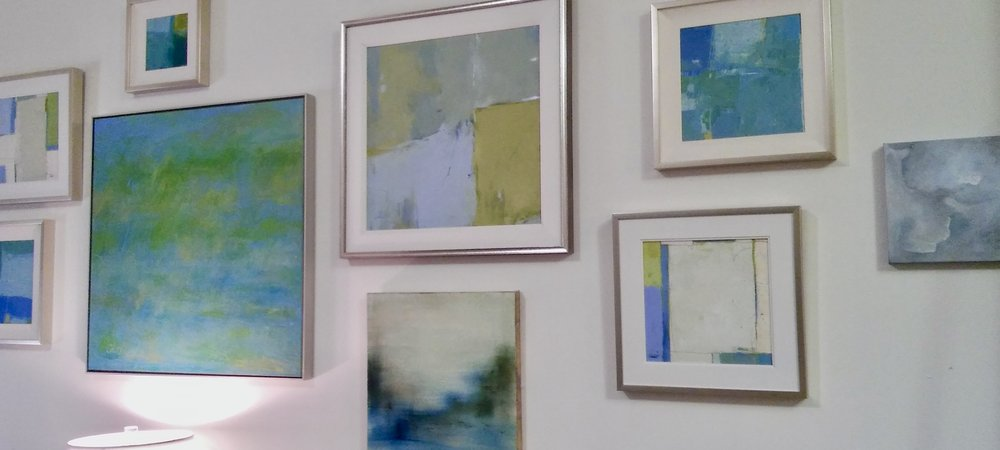 Wall of abstracts installed for Marketplace Interiors of Tampa, featuring original works by Sally Cahill, Katie White and Maggie Grier.