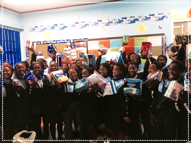 Girls from Imbasa Primary School in Cape Town holding their donated pads and other hygienic supplies
