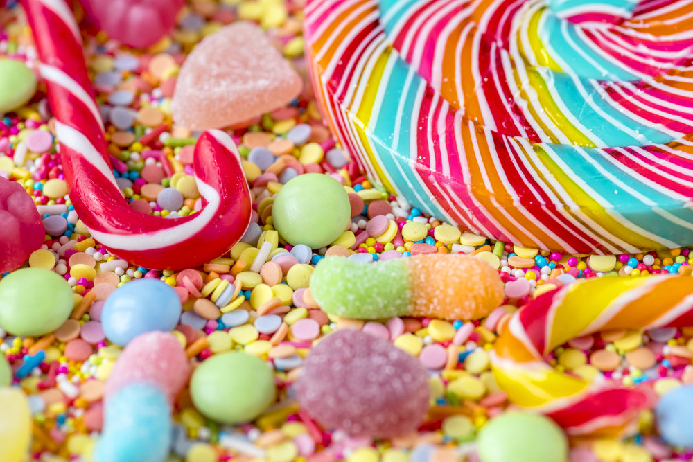 Close up of candycane and lollipop on a colorful sweets backgrou